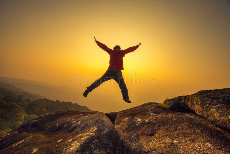 Mostre em silhueta o homem que salta no céu do por do sol imagens de stock