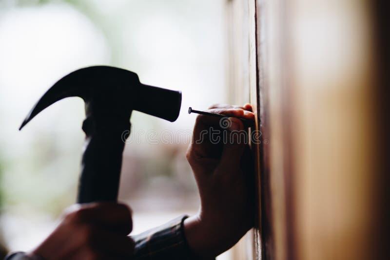 Mostre em silhueta o martelamento do prego na parede, melhoria home fotos de stock royalty free