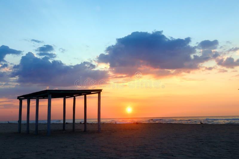 Mostre em silhueta o miradouro em um Sandy Beach vazio no por do sol imagem de stock