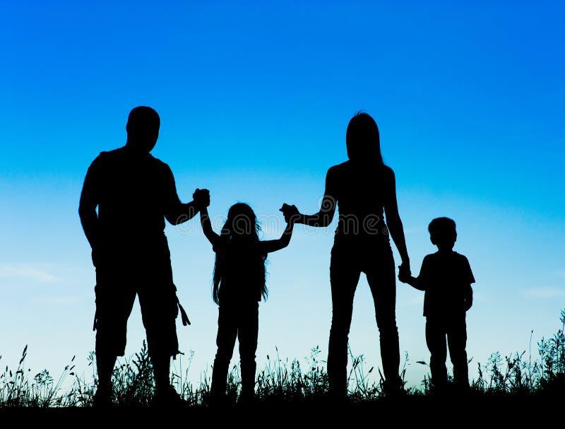 mostre em silhueta o pai, a mãe e as crianças guardando as mãos no por do sol fotografia de stock royalty free