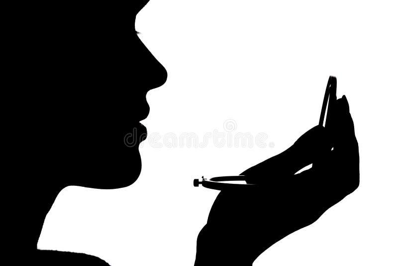 Mostre em silhueta o perfil de uma cara da mulher que olha em um espelho do bolso, no conceito da beleza e na forma fotos de stock