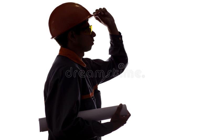 Mostre em silhueta o perfil do trabalhador da construção com projeto nas mãos, homem nos macacões no fundo isolado branco, concei imagem de stock