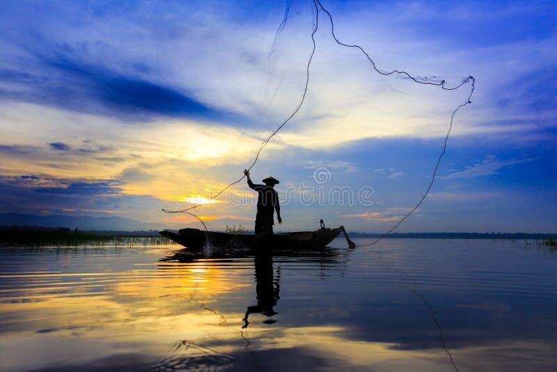 Mostre em silhueta o pescador asiático no barco de madeira que molda uma rede para o catc imagem de stock