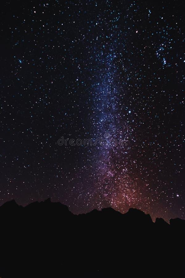 Mostre em silhueta o pico de montanha na noite com o céu completo das estrelas e da Via Látea fotos de stock