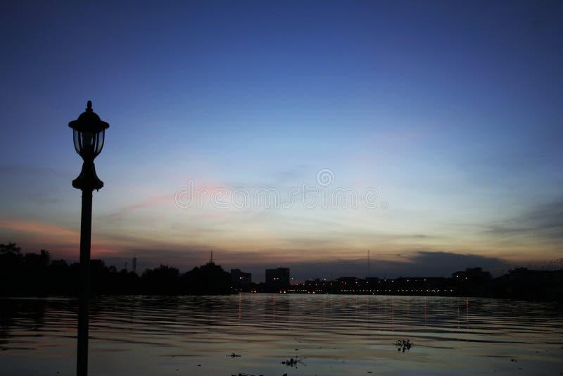 Mostre em silhueta o polo bonde que está no rio de Bangpakong no fotos de stock