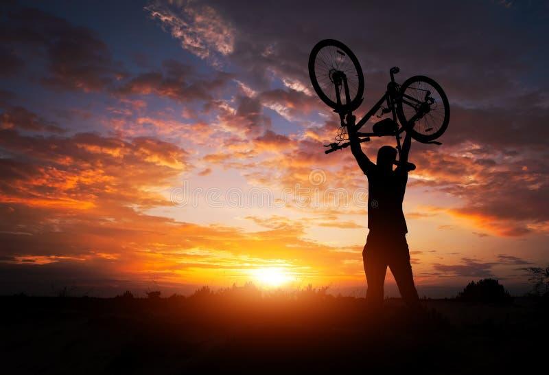 Mostre em silhueta o suporte do homem na bicicleta de levantamento da a??o acima de sua cabe?a no prado com por do sol imagem de stock royalty free