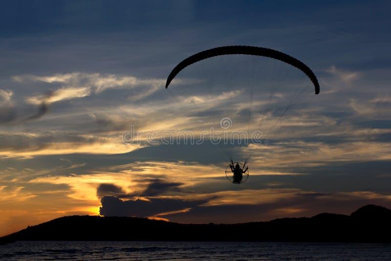 Mostre em silhueta o voo do paramotor/paraglider no céu com seavie foto de stock