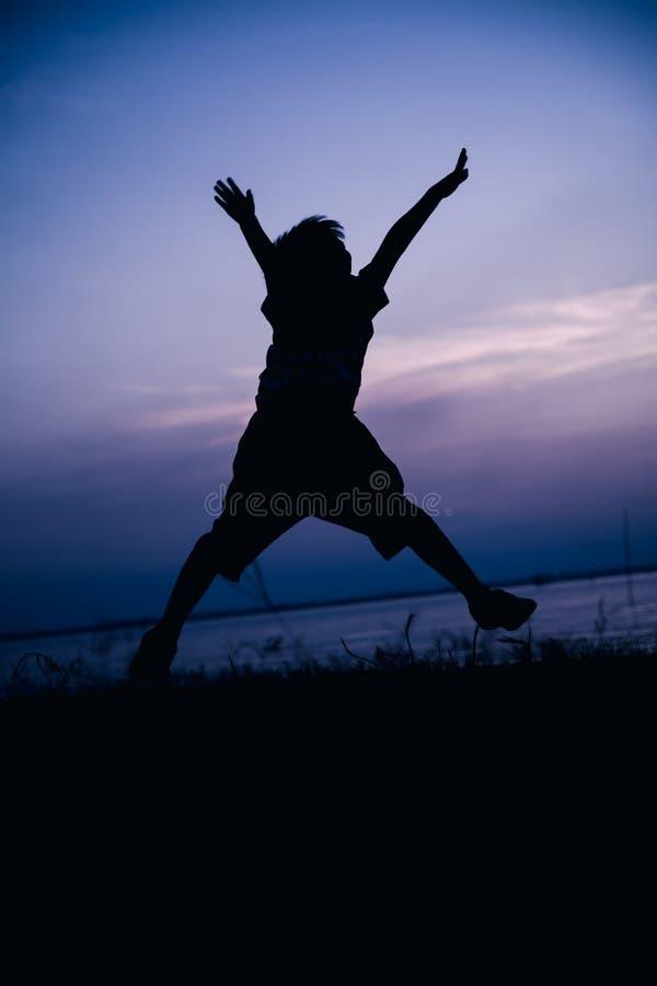 Mostre em silhueta a opinião traseira a criança que aprecia e que salta no beira-rio fotografia de stock royalty free