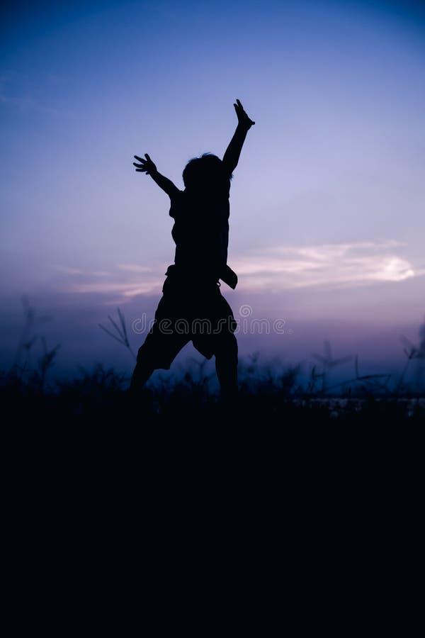 Mostre em silhueta a opinião traseira a criança que aprecia e que salta no prado Co imagens de stock royalty free