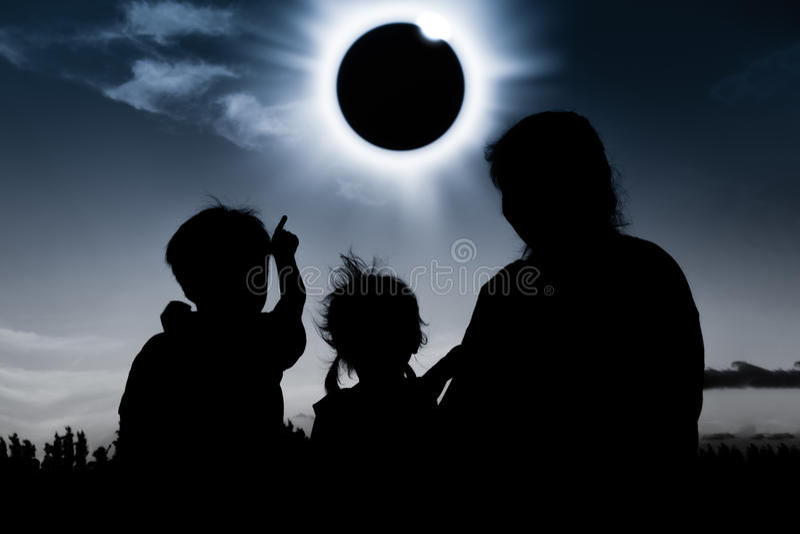Mostre em silhueta a opinião traseira a família que olha o eclipse solar na obscuridade