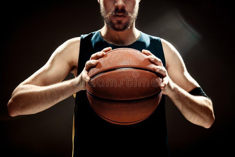 Mostre em silhueta a opinião um jogador de basquetebol que guarda a bola da cesta no fundo preto imagens de stock