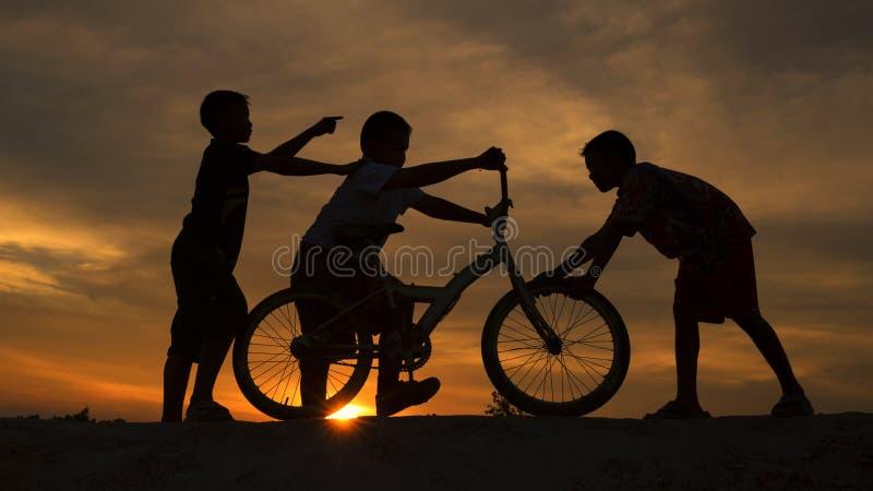 Mostre em silhueta os meninos alegres com uma bicicleta foto de stock