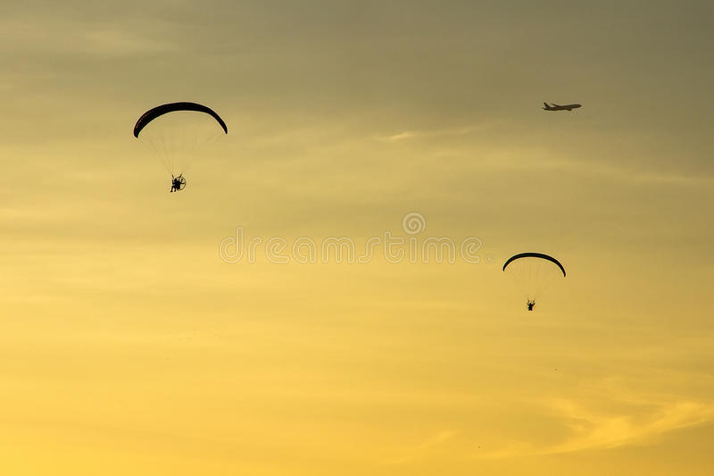 Mostre em silhueta Paramotor, paraquedas, voo de Paraglide no por do sol imagens de stock royalty free