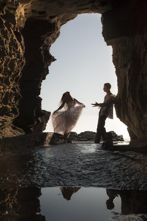 Mostre em silhueta pares nupciais bonitos novos na arcada da rocha na praia foto de stock