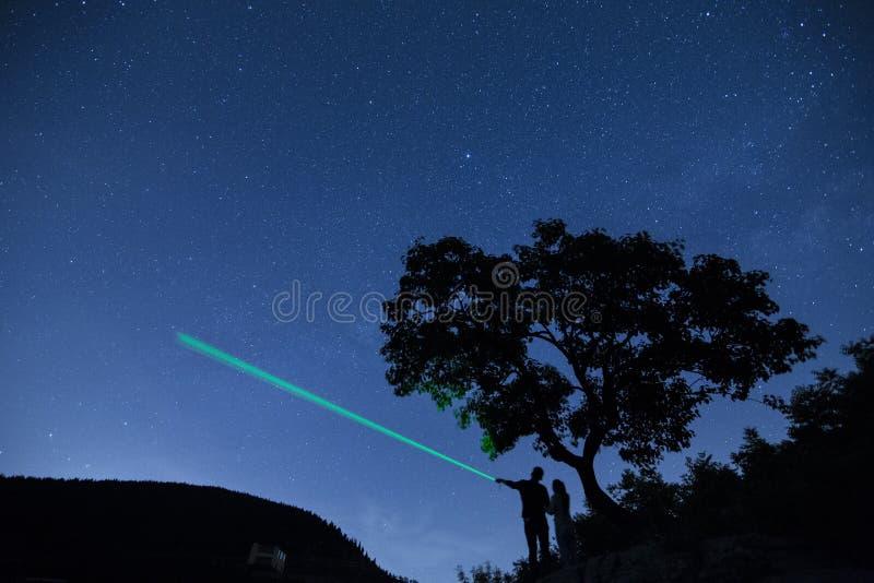 Mostre em silhueta pares sob uma árvore e a apreciação do céu estrelado no cabo das noites imagens de stock royalty free