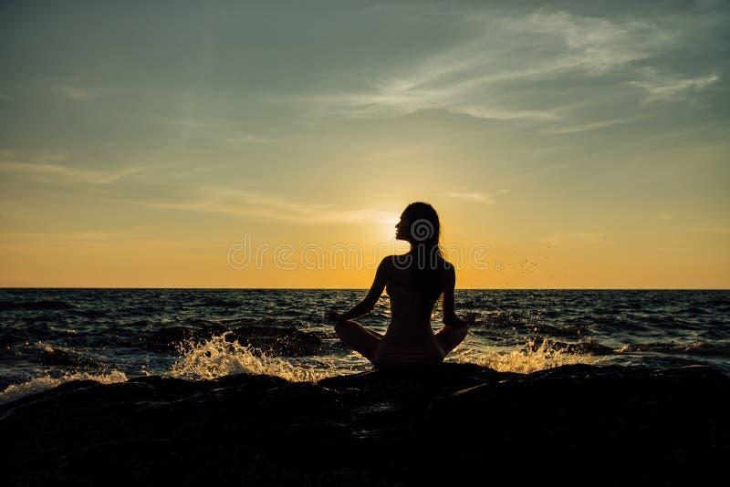 Mostre em silhueta a posição dos lótus da menina da meditação sobre a pedra no fundo do mar impressionante foto de stock royalty free