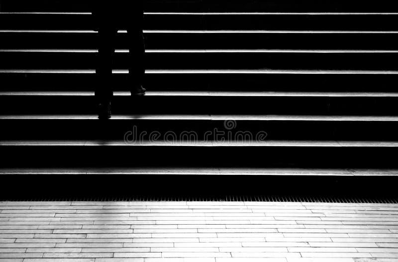 Mostre em silhueta a sombra de uma pessoa que anda acima das escadas da cidade fotografia de stock royalty free