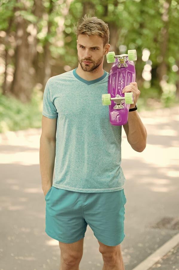 Mostrer? il suo meglio in skateboarding Il tipo porta il bordo del penny pronto a guidare Il fronte serio dell'uomo porta il parc immagini stock