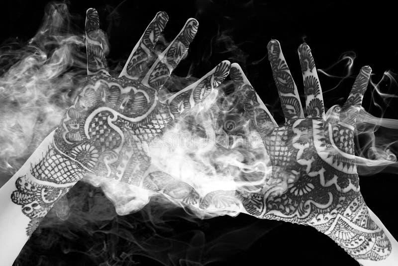 Mostri il bello tatuaggio del hennè alla mano aperta con fumo e immagine stock