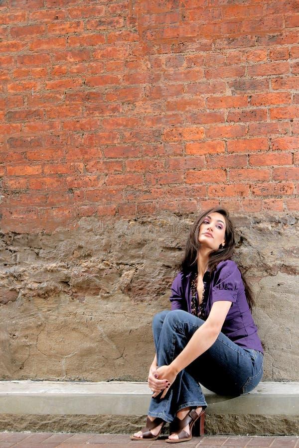 mot att sitta för tegelsten wall kvinnan fotografering för bildbyråer