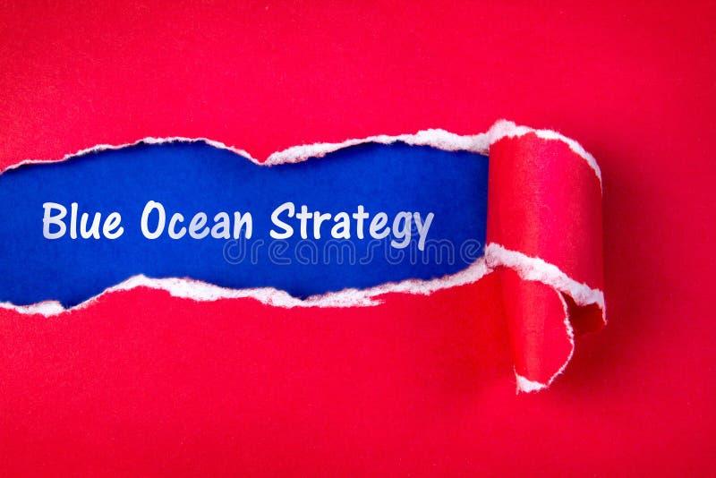 Mot bleu de stratégie d'océan sur le papier rouge déchiré et espace avec un bleu images libres de droits
