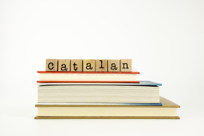 Mot catalan de langue sur des timbres et des livres en bois photos stock