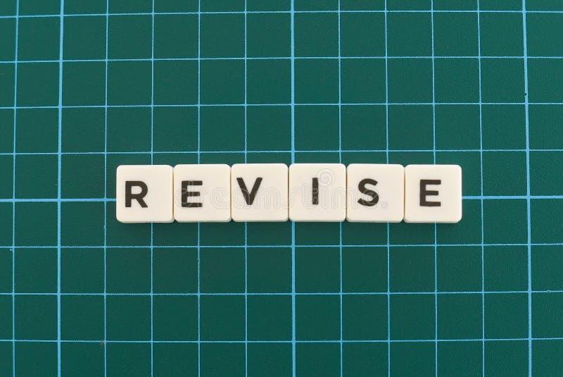 Mot d'épreuve de révision fait en mot carré de lettre sur le fond carré vert de tapis photos stock