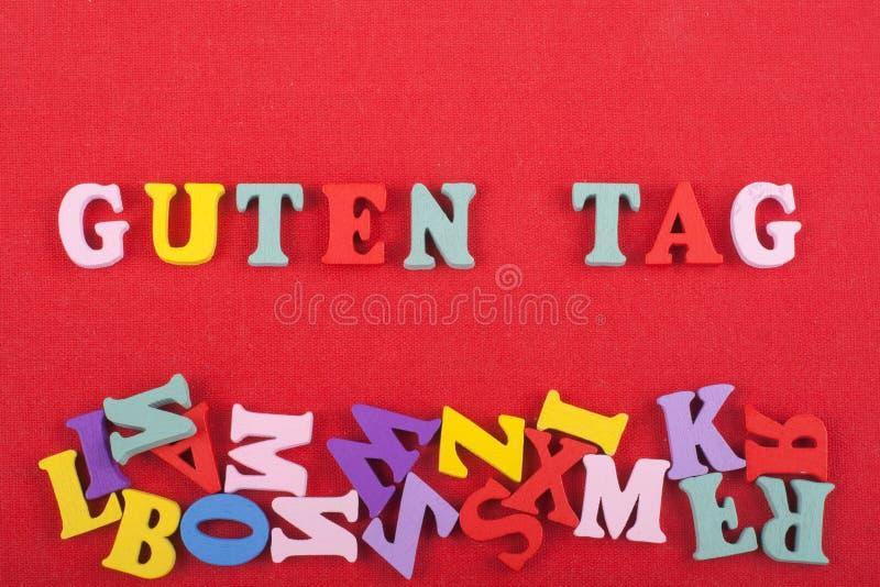 Mot d'ÉTIQUETTE de GUTEN sur le fond rouge composé des lettres en bois d'ABC de bloc coloré d'alphabet, l'espace de copie pour le images libres de droits