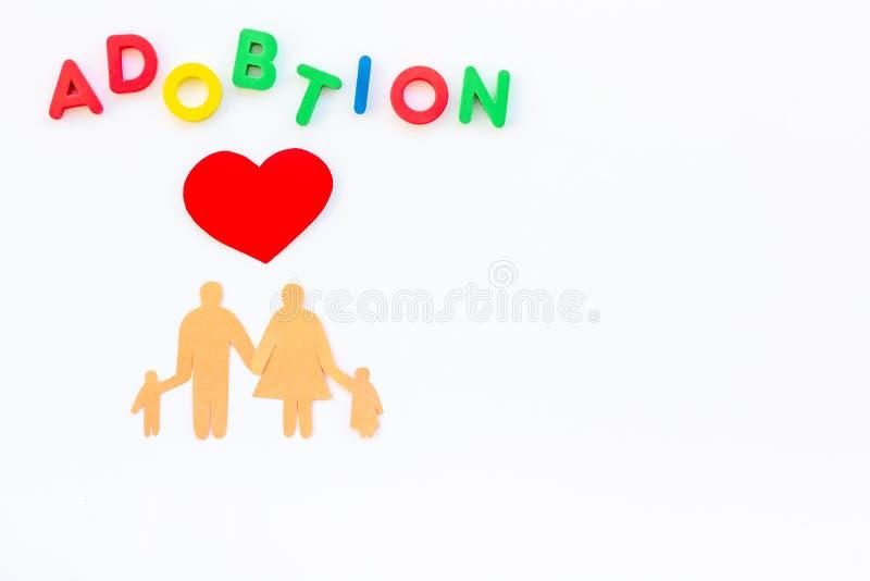 Mot d'adoption et chiffre de famille pour adopter le concept d'enfant sur la moquerie blanche de vue supérieure de fond  photo stock