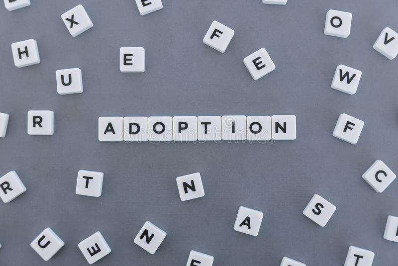 Mot d'adoption fait en mot carr? de lettre sur le fond gris images libres de droits