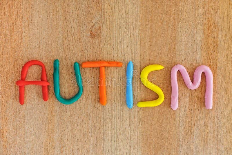 Mot d'autisme fait en pâte de jeu Fond en bois photographie stock