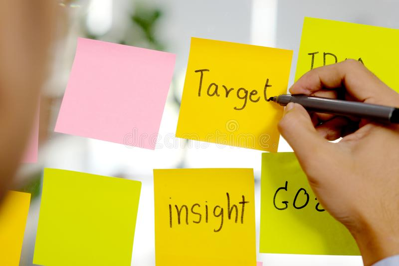 Mot de cible d'écriture de main d'homme sur la note collante au bureau, affaires faisant un brainstorm des idées créatives, mode  images stock