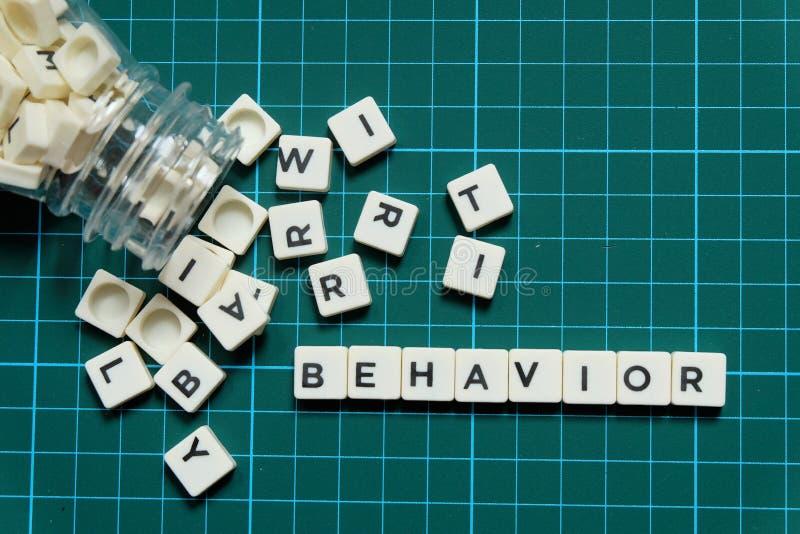 Mot de comportement fait en mot carré de lettre sur le fond carré vert de tapis photos libres de droits