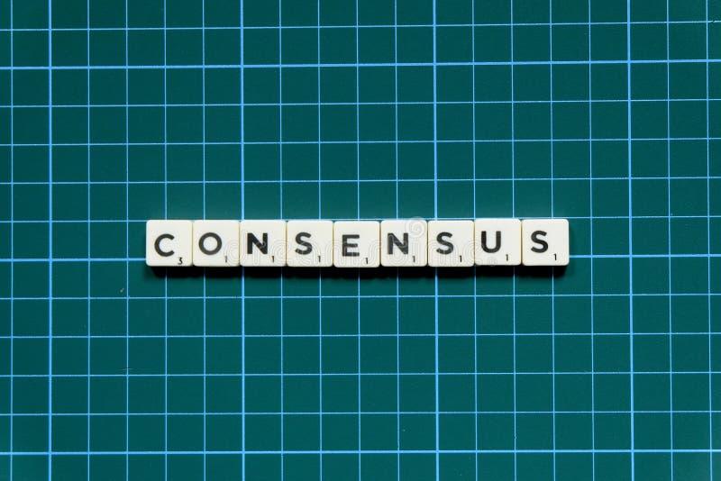 Mot de consensus fait en bloc carré de lettre sur le fond carré vert de tapis image stock