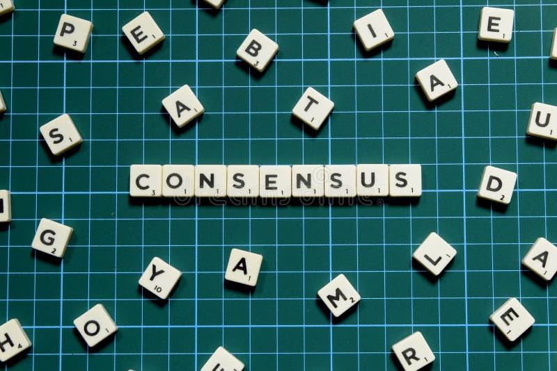 Mot de consensus fait en bloc carré de lettre sur le fond carré vert de tapis images stock