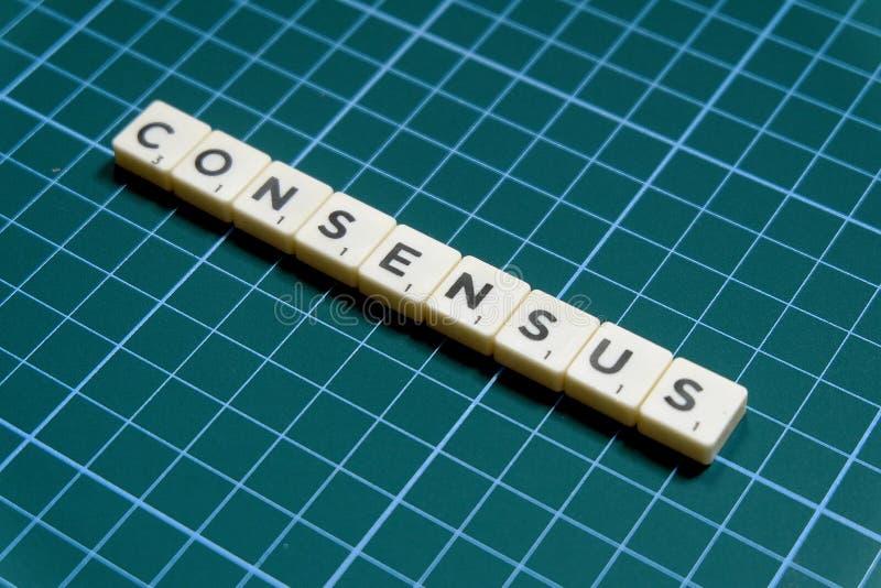 Mot de consensus fait en bloc carré de lettre sur le fond carré vert de tapis photo stock