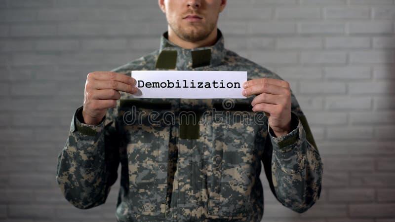 Mot de démobilisation écrit sur des mains de signe dedans du soldat masculin, fin de terme photo stock