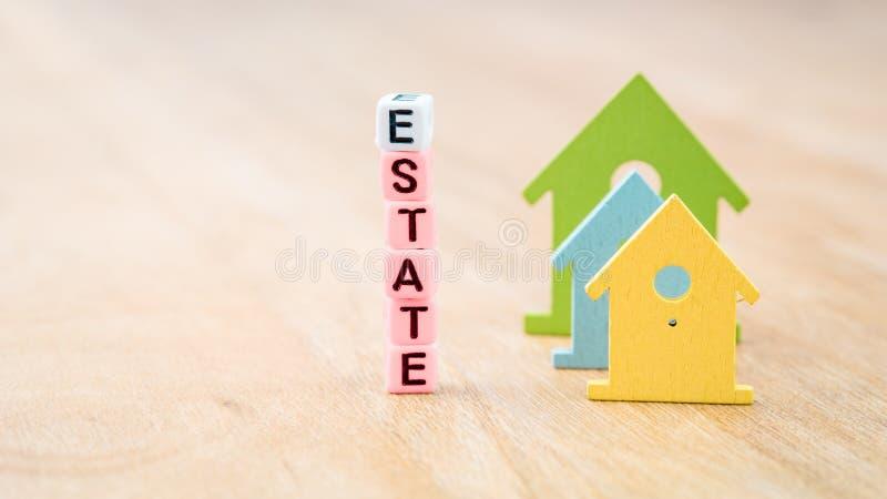Mot de DOMAINE des lettres de cube derrière des symboles colorés de maison sur la surface en bois Concept photo libre de droits