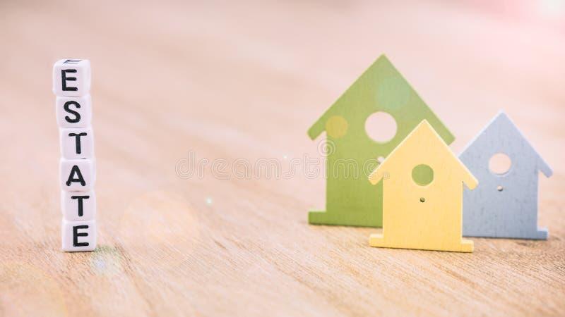 Mot de DOMAINE des lettres de cube derrière des symboles colorés de maison sur la surface en bois Concept L'espace libre entre photos stock