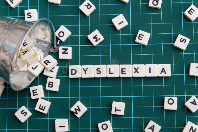 Mot de dyslexie fait en mot carré de lettre sur le fond carré vert de tapis photographie stock