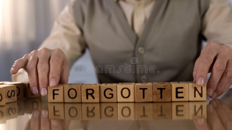 Mot de fabrication masculin plus âgé oublié des cubes en bois sur la table, désordre de démence photo stock