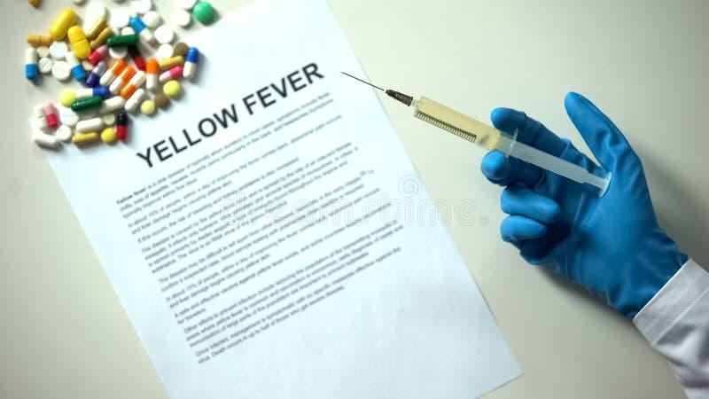Mot de fièvre jaune sur le papier, la main de docteur avec des pilules de seringue et les comprimés sur la table photographie stock