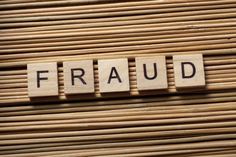 Mot de FRAUDE écrit sur les cubes en bois Concept de finances Argent image libre de droits