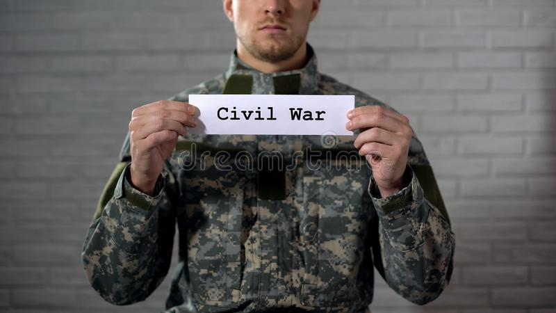 Mot de guerre civile écrit sur des mains de signe dedans du soldat masculin, de la cruauté et de la mort photos libres de droits