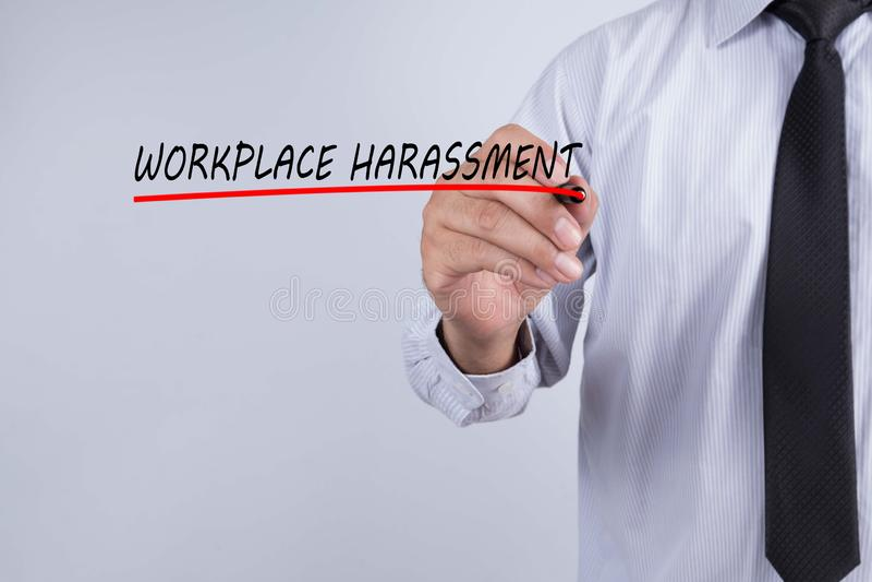 Mot de harcèlement de lieu de travail d'écriture de main d'homme d'affaires avec le marqueur rouge sur le panneau transparent de  photographie stock