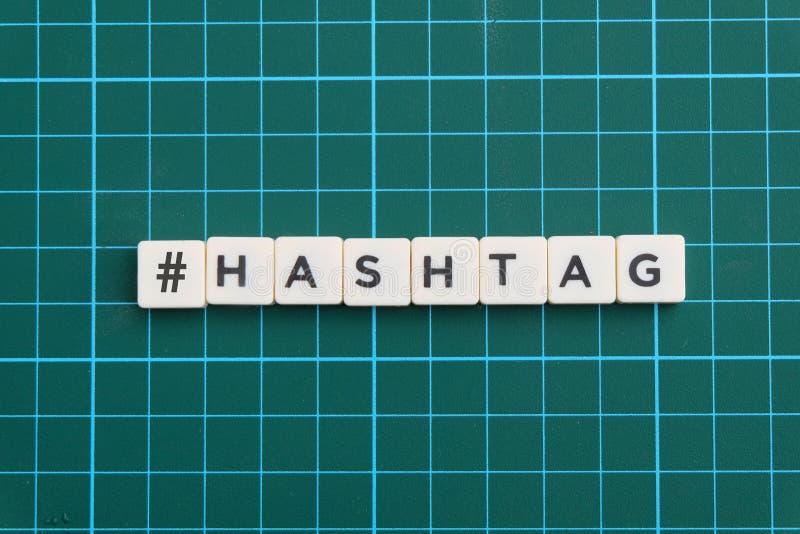 Mot de Hashtag fait en mot carré de lettre sur le fond carré vert de tapis photo libre de droits