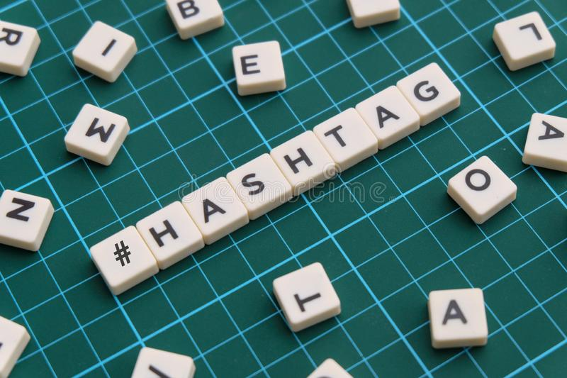 Mot de Hashtag fait en mot carré de lettre sur le fond carré vert de tapis image libre de droits