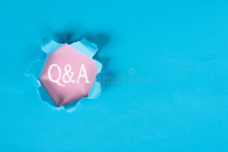 Mot de indication de papier déchiré bleu de Q&A sur le papier rose photographie stock libre de droits
