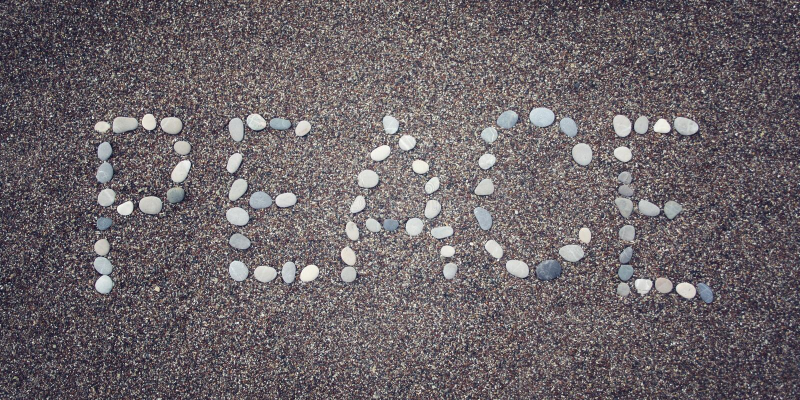 Mot de 'paix' sur le sable Écrit avec des cailloux Photo âgée photo stock