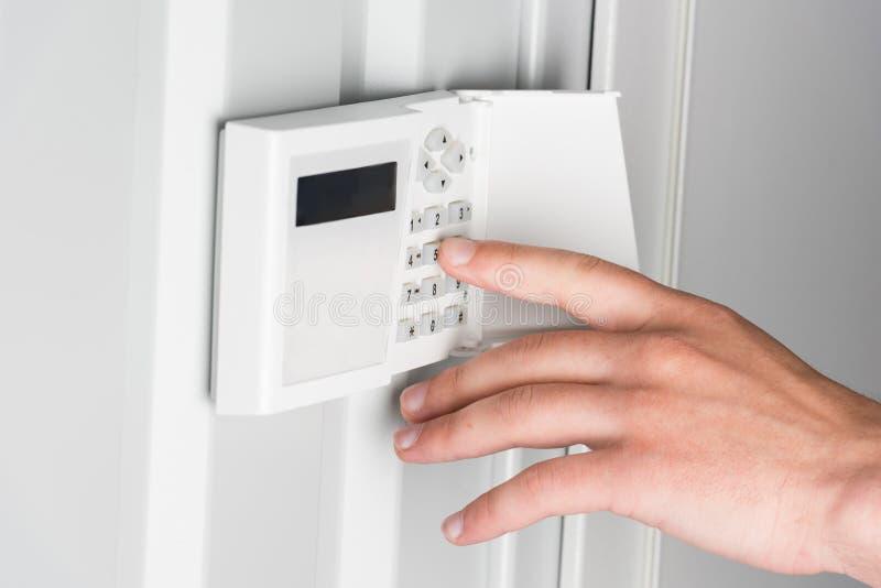 Mot de passe de dactylographie de personne sur l'alarme de sécurité à la maison, concept de système de sécurité images stock